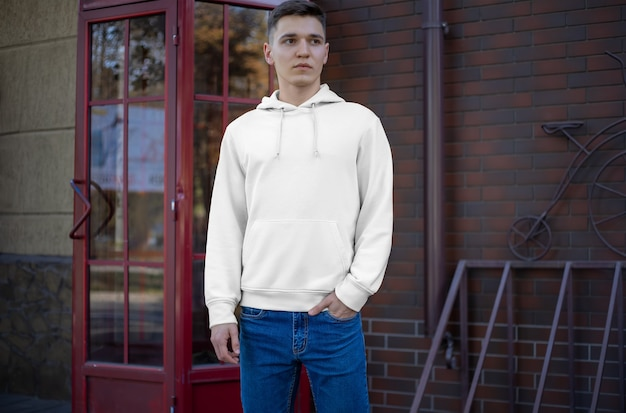 Prezentacja białej bluzy z kapturem na młodym chłopaku na ulicy, widok z przodu. makieta modnych ubrań na reklamę w sklepie. wzór do noszenia na co dzień dla swojego projektu.