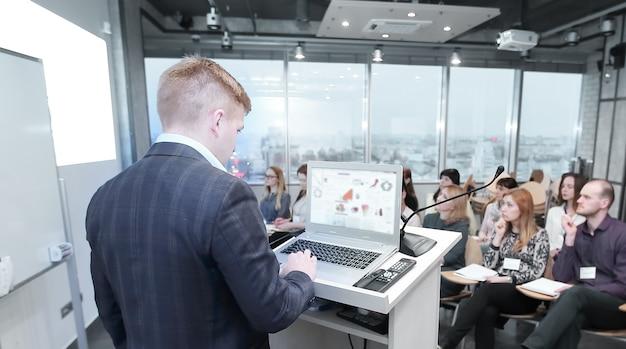 Prezentacja biznesowa.biznesmen składa raport pracownikom firmy.