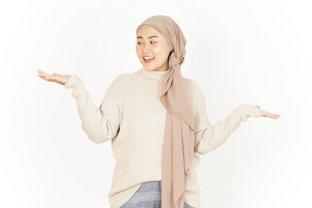 Prezentacja i pokazanie dwóch produktów na dłoni pięknej azjatyckiej kobiety w hidżabie