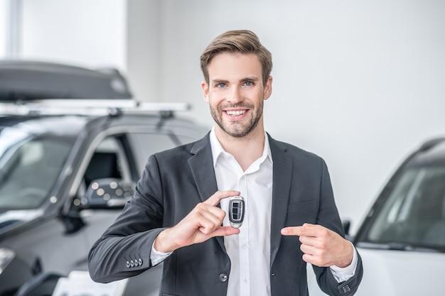 Prezentacja. radosny atrakcyjny młody mężczyzna w białej koszuli i ciemnym garniturze, trzymający brelok i wskazujący palcem stojący w salonie samochodowym