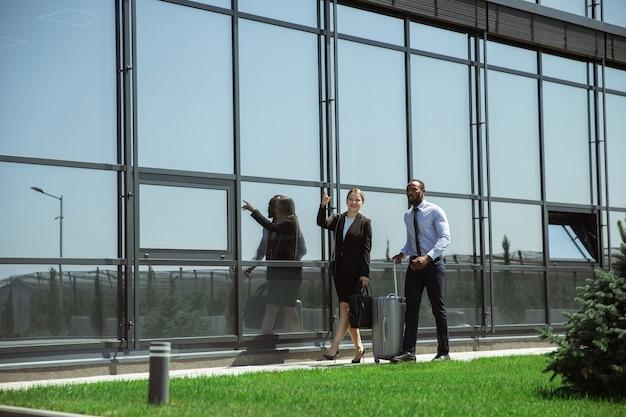 Prezentacja. spotkanie młodych partnerów biznesowych po dotarciu do miejsca zakończenia podróży służbowej. mężczyzna i kobieta spaceru przed szklaną ścianą tle nowoczesnego budynku. pojęcie biznesu, finansów, reklamy.