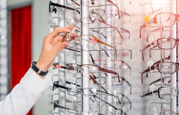 Prezentacja z okularami w nowoczesnym sklepie okulistycznym. ręce w okularach. wiersz okularów u optyka. sklep z okularami. stojak z okularami w sklepie z optyką. zbliżenie.