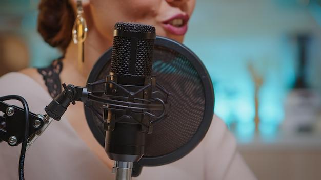Prezenter nagrywa głos w domowym studiu dla mediów przy użyciu profesjonalnego mikrofonu. twórczy wpływowy program online, produkcja internetowa na antenie internetowej, gospodarz programu transmitującego treści na żywo, nagrywanie