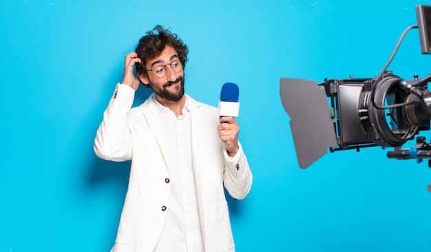 Prezenter telewizyjny młody brodaty mężczyzna.
