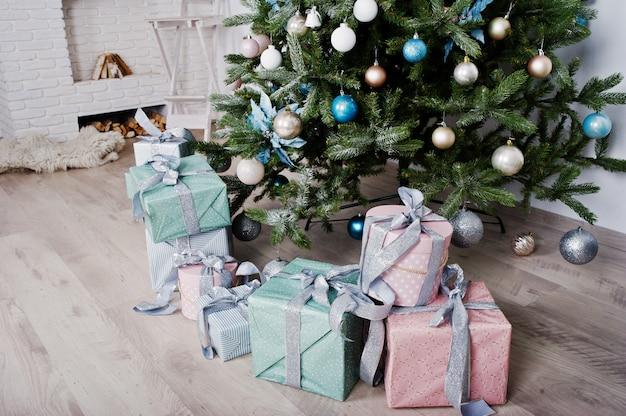 Prezentów pudełka pod nowego roku drzewem przy białym pokojem