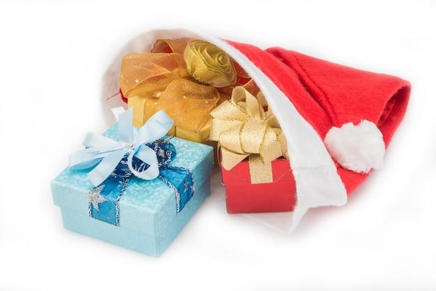 Prezentów pudełka w czerwonym santa kapeluszu na białym tle