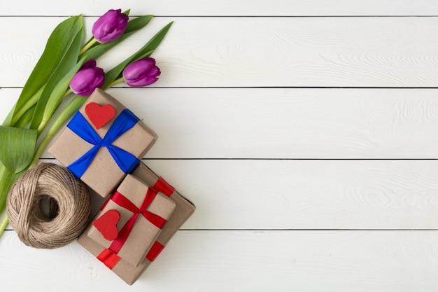 Prezentów pudełka z kwiatami na białej drewnianej ścianie