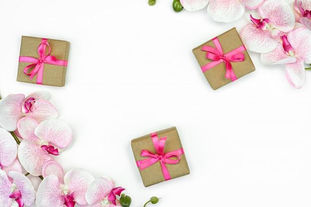 Prezentowe pudełka z różową wstążką i kwiatami orchidei