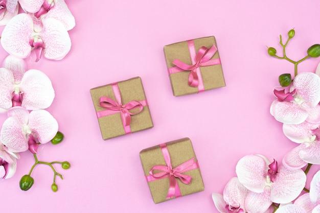 Prezentowe pudełka z różową wstążką z kwiatami orchidei na różowym tle