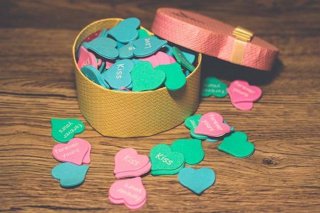Prezentowe różowe pudełko w kształcie serca wypełnione wielokolorowymi małymi sercami na drewnianym