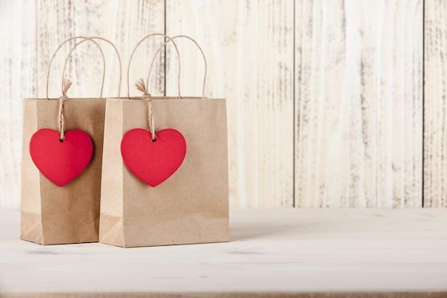Prezentowe torby kartonowe z metkami w kształcie serca na drewnianym tle