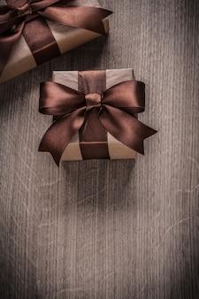 Prezentuje pudełka z brązowymi wstążkami koncepcji uroczystości w wersji pionowej