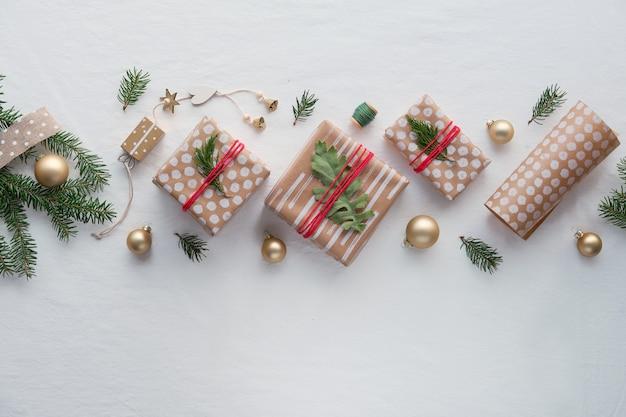 Prezenty bożonarodzeniowe diy w rzemieślniczym papierze do pakowania, ręcznie robione dekoracje. mieszkanie leżało na tle białej miękkiej tkaniny.