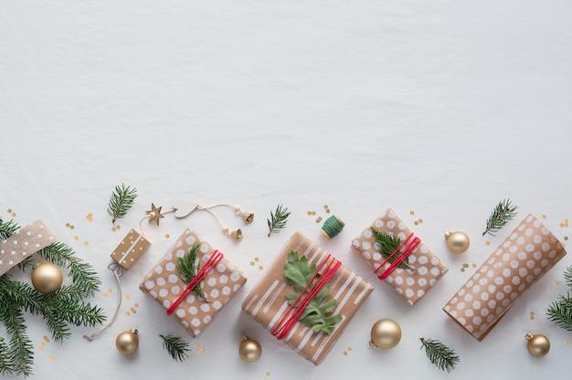Prezenty bożonarodzeniowe diy w rzemieślniczym papierze do pakowania, ręcznie robione dekoracje. płasko leżał na białym miękkim obrusie tekstylnym.