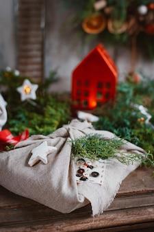 Prezenty bożonarodzeniowe owinięte tkaniną furoshiki w stylu japońskim w iglaste gałęzie jodły i świerku. przygotowanie i projekt wakacji noworocznych. ręcznie robione w stylu rustykalnym, pomysły tanie