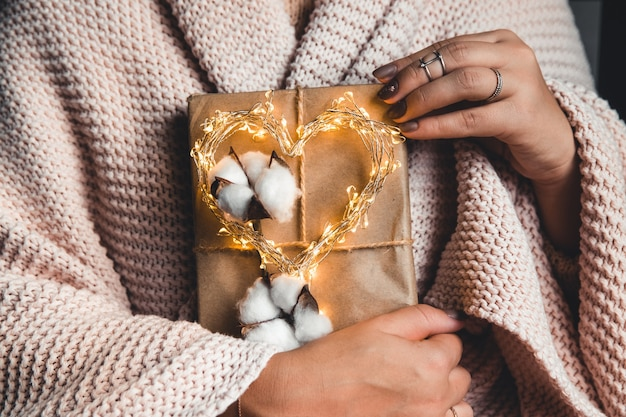 Prezenty czasu - pudełko w ręce dziewczyny. prezent w rękach kobiety. pled, bawełna, manicure. walentynki