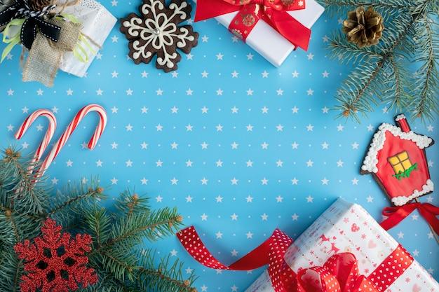 Prezenty, gałęzie jodły ze stożkiem jodły, piernik śnieżynka, piernik domu, cukierki i bombki na niebieskim tle z wzorem gwiazd. boże narodzenie, zima, koncepcja nowego roku. widok z góry
