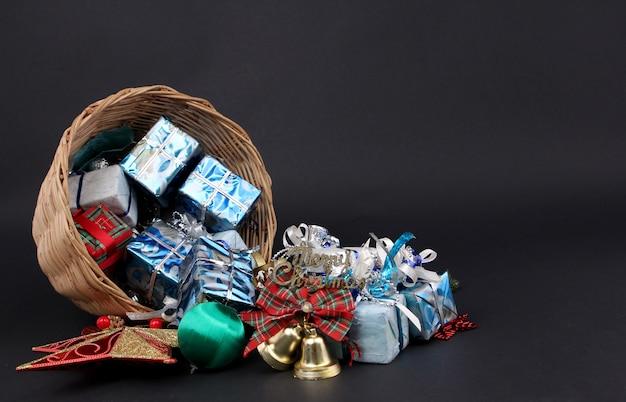 Prezenty i dekoracje w koszyku świątecznym z czarnym tłem.
