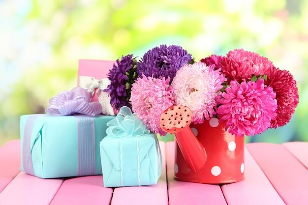 Prezenty i kwiaty w konewce, na tle przyrody