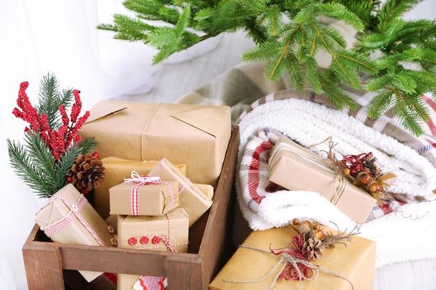 Prezenty i ozdoby świąteczne w pudełkach obok choinki na jasnej powierzchni