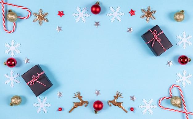 Prezenty i wzór ze złotych, czerwonych ozdób i płatków śniegu na pastelowym niebieskim tle.