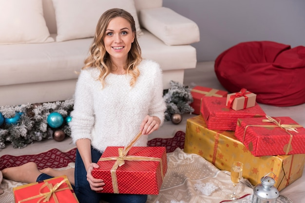 Prezenty na boże narodzenie. urocza, miła zachwycona kobieta siedząca wśród pudełek z prezentami i uśmiechnięta podczas rozpakowywania prezentu