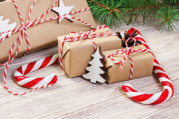 Prezenty na boże narodzenie z jodłą i ozdobnym stożkiem, słodycze i prezenty na święta, kolorowe cukierki, płatki śniegu, boże narodzenie i szczęśliwego nowego roku, układanie płasko, widok z góry