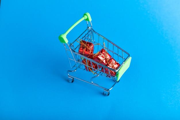 Prezenty na zakupy świąteczne koncepcji. akcesoria koszykowe i świąteczne. świąteczny kosz z prezentami. onlain zakupy. na niebiesko. miejsce do pisania.