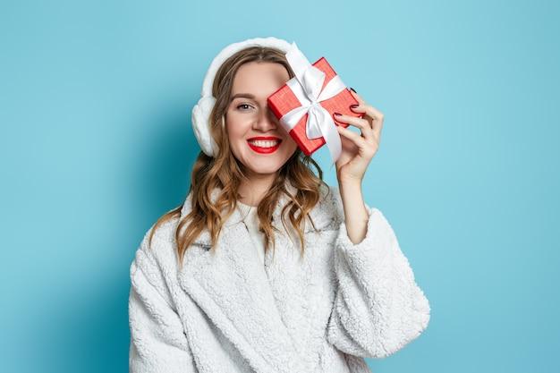 Prezenty noworoczne 2021. młoda szczęśliwa uśmiechnięta kobieta w białym futrze ze sztucznego futra i futrzanych słuchawkach zamyka oczy pudełkiem prezentowym i uśmiecha się na niebieskiej ścianie. skopiuj miejsce