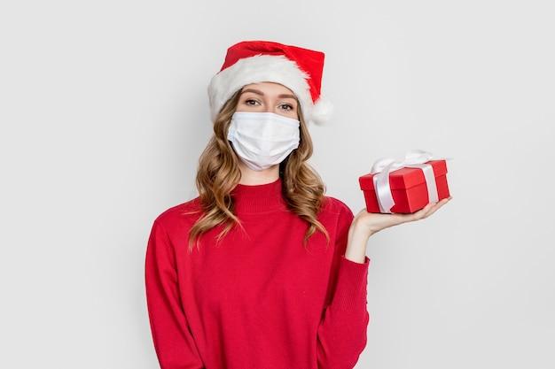 Prezenty noworoczne 2021 z okazji pandemii kwarantanny koronawirusa. dziewczyna studentka w czerwonym swetrze założonym w maskę medyczną i santa hat trzyma pudełko na białym tle na tle białego studia.