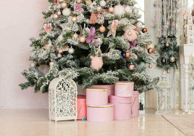 Prezenty noworoczne i świąteczne w kolorze różowym pod dużą pięknie zdobioną choinką