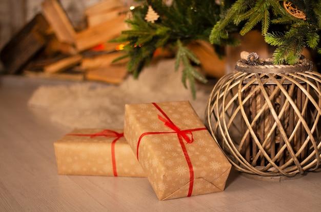 Prezenty noworoczne i wiklinowy kosz pod piękną choinką z kominkiem i szarym tle ceglanego muru.