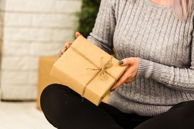 Prezenty noworoczne pod choinką. prezenty są pakowane w papier pakowy i wiązane