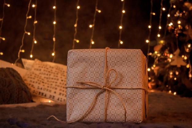 Prezenty noworoczne w markowym papierze i jasne wstążki znajdują się pod choinką