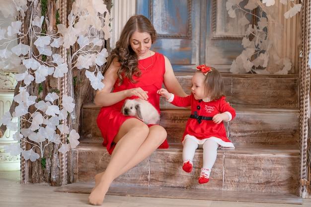 Prezenty od mikołaja na boże narodzenie. mała dziewczynka dostała na boże narodzenie puszystego króliczka.