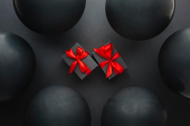 Prezenty otoczone czarnymi balonami