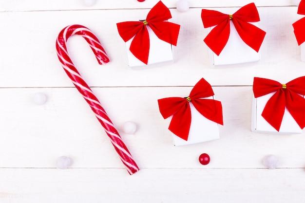Prezenty świąteczne, białe małe pudełka z czerwoną kokardką i cukierki na białym tle drewnianych
