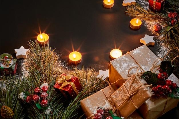 Prezenty świąteczne, choinka, świece, kolorowy wystrój, gwiazdy, kulki na czarnym tle. widok z góry. skopiuj miejsce. martwa natura mieszkanie leżało nowy rok