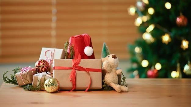 Prezenty świąteczne, czapka mikołaja i misia na drewnianym stole w salonie.