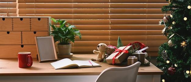 Prezenty świąteczne, filiżanka kawy i notatnik na drewnianym stole w salonie.