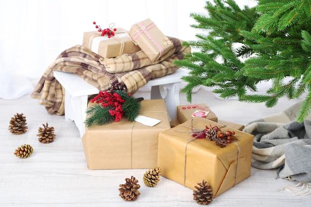 Prezenty świąteczne i ozdoby w pudełkach w pobliżu choinki na jasnym tle
