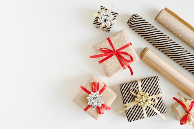 Prezenty świąteczne i papier pakowy w rolkach na białym tle. pudełka na prezenty diy