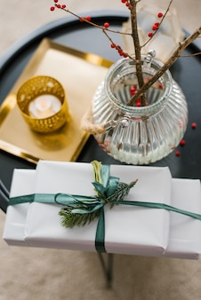 Prezenty świąteczne i wazon z gałązką czerwonych jagód na stoliku w salonie, udekorowany na boże narodzenie i nowy rok