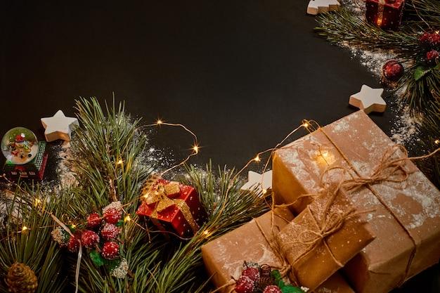 Prezenty świąteczne i wianek w pobliżu zielonej gałęzi świerku na czarnym tle. boże narodzenie tło. widok z góry. skopiuj miejsce. martwa natura. leżał płasko. nowy rok