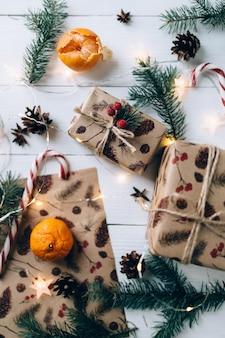 Prezenty świąteczne, lizak, mandarynka na białym drewnianym stole.