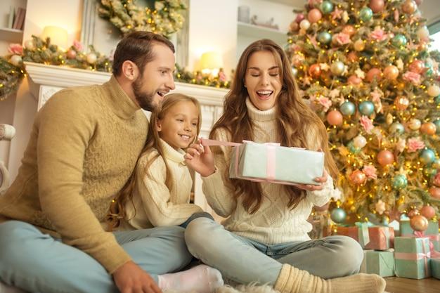 Prezenty świąteczne. młoda rodzina czuje się szczęśliwie otwierająca prezenty świąteczne