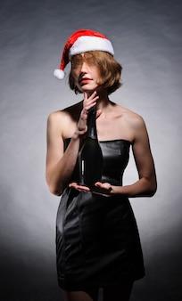 Prezenty świąteczne. model dziewczyna w santa hat. dziewczyna trzyma szampana i okulary, na białym tle