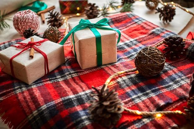 Prezenty świąteczne na tle czerwonej wełnianej kratki w kratę z girlandami szyszek i gałęzi jodłowych