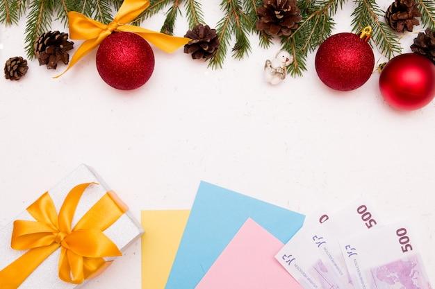 Prezenty świąteczne nowy rok, pieniądze, banknoty euro, pudełko na prezenty, złota wstążka, zabawki świąteczne, gałązki świerkowe, widok z góry, miejsce na kopię