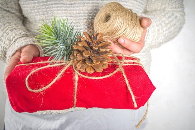 Prezenty świąteczne owinięte tkaniną. koncepcja zrównoważonego wykorzystania i zero odpadów wielokrotnego użytku, tekstylne opakowanie prezentowe z recyklingu. ekologiczne tradycje i dekoracje świąteczne. prezenty świąteczne w stylu japońskiego furoshiki